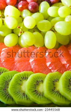 Tasty fruit salad on tray. Multiple fruits. - stock photo