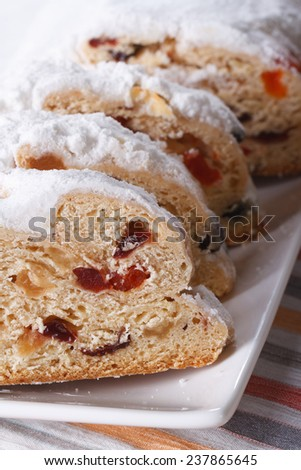 Tasty German Christmas fruit bread Stollen sliced macro on a white plate. vertical