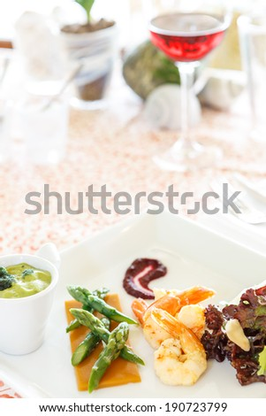 Tasty gourmet seafood starter of grilled prawn or shrimp with green asparagus spears and lettuce - stock photo
