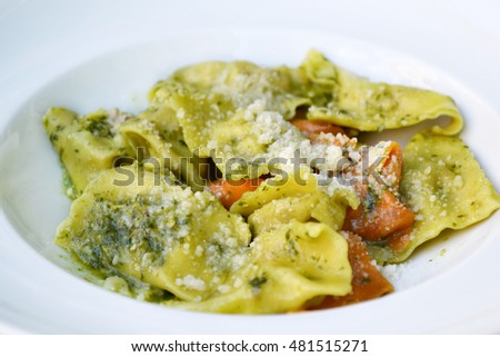 Tasty green and red ravioli with pesto sauce