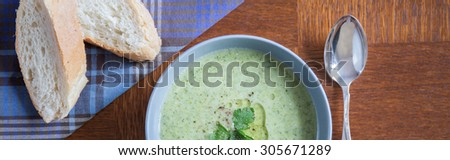 Tasty green soup served with a french baguette - stock photo