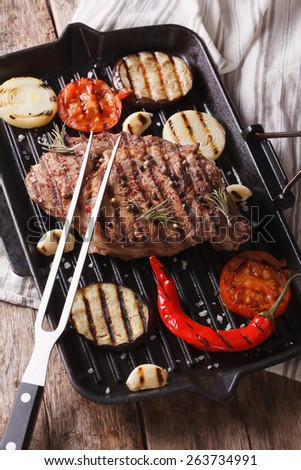 Tasty grilled beef steak and onions, eggplant, chili peppers on the grill pan closeup. vertical  - stock photo