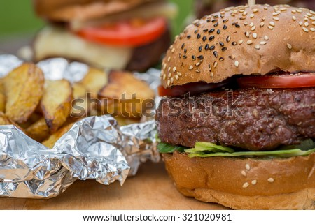 Tasty grilled burger, fried potato and glass of cold beer. tasty summer symbol. Selective focus - stock photo