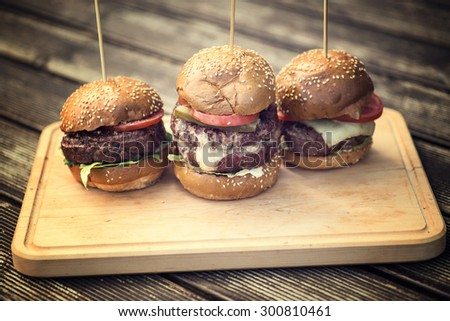 Tasty grilled burger on a wooden table. tasty summer symbol. Selective focus and toned photo - stock photo