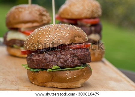 Tasty grilled burger on wooden table. tasty summer symbol. Selective focus - stock photo