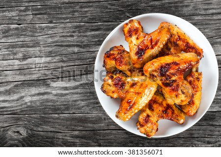 tasty grilled chicken wings on a white dish, top view - stock photo