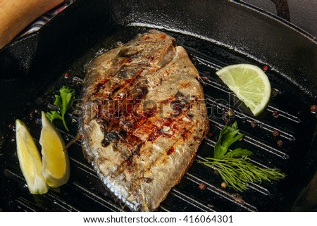 Tasty grilled fish (Vomer) on the barbeque pan with dill and lime.Clsoeup/ - stock photo