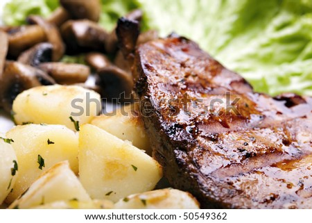 Tasty grilled food, chicken meat, roasted potatoes and mushrooms and sallet - stock photo