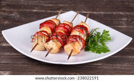 Tasty grilled meat and vegetables on skewer on plate - stock photo