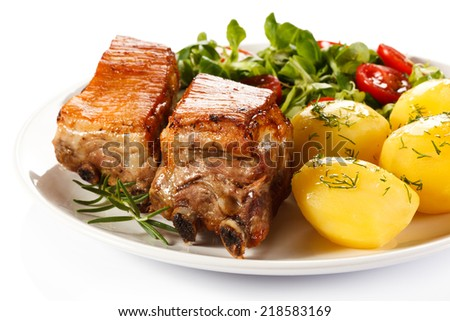 Tasty grilled ribs with vegetables on white background