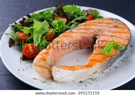 Tasty grilled salmon with salad on table close up