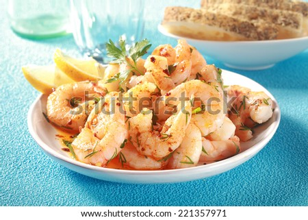 Tasty grilled shelled pink shrimps or prawns seasoned with olive oil and herbs served as a seafood starter to a meal on a textured blue table - stock photo