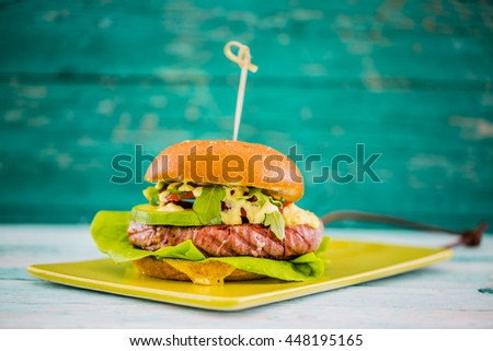 Tasty grilled tuna burger with lettuce and mayonnaise served on wooden table  - stock photo