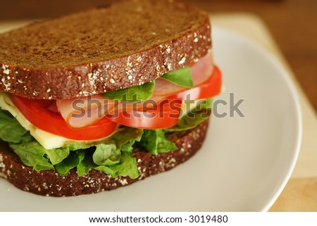 Tasty ham and cheese sandwich. Very shallow depth of field. - stock photo