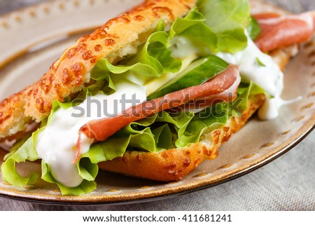 Tasty ham Prosciutto sandwich with salad leaf, cheese and cucumber sauce in a cheese bread, homemade on breakfast.