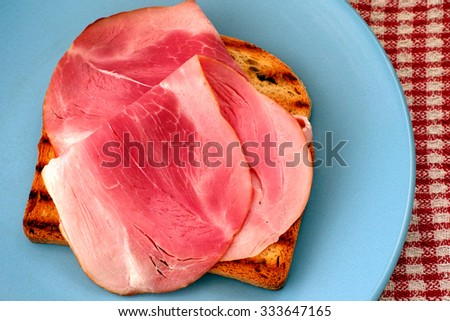Tasty ham slices on toasted bread slice.