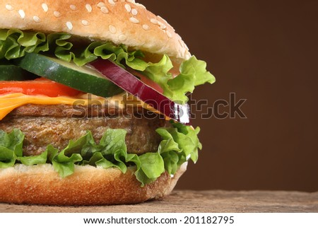 Tasty hamburger on wood background. Lots of ingredients - stock photo