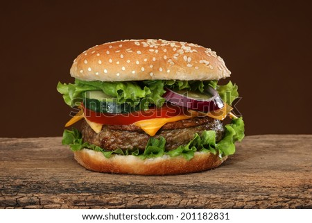 Tasty hamburger on wood background. Lots of ingredients - stock photo