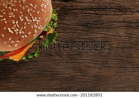 Tasty hamburger on wood background. Space for text - stock photo