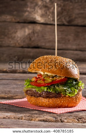 Tasty hamburger on wooden stick. Old table with big burger. Special sauce and juicy meat. Food that's bad for health. - stock photo