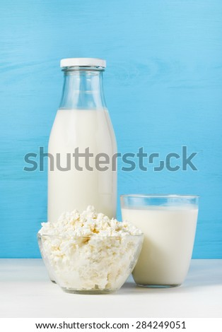 tasty healthy dairy products on a white table on a blue background:  cottage cheese in bowl,  milk in a glass bottle and in a glass