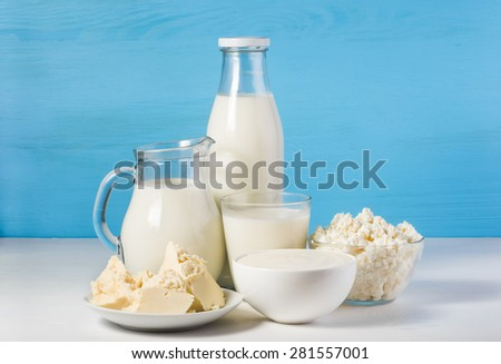 tasty healthy dairy products on a white table on a blue background: sour cream in a white bowl, cottage cheese in bowl, butter on a saucer and milk in a jar, glass bottle and in a glass