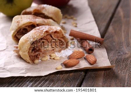 Tasty homemade apple strudel  on paper napkin, on wooden background - stock photo