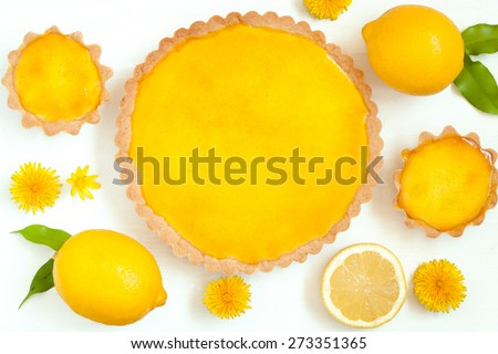 Tasty homemade backed lemon tart pie dessert with narcissus flowers on white rustic background table - stock photo