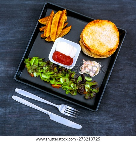 Tasty homemade burger with  lettuce, onion and tomatoes on blackboard. - stock photo