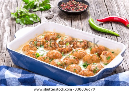 tasty homemade meatballs smothered in a creamy gravy sauce with parsley and spices in the baking dish, on the wooden background, classic recipe, close-up - stock photo
