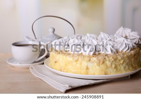Tasty homemade meringue cake and cup of tea on wooden table, on light background - stock photo