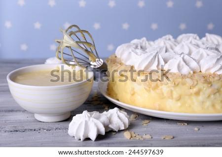 Tasty homemade meringue cake on wooden table, on blue background - stock photo