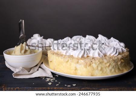 Tasty homemade meringue cake on wooden table, on grey background - stock photo