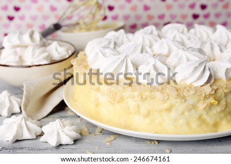 Tasty homemade meringue cake on wooden table, on pink background - stock photo
