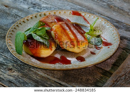 Tasty homemade pancakes on plate with syrup and mint on old wooden boards - stock photo