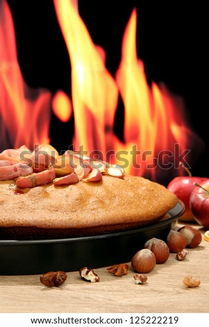 tasty homemade pie with apples and nuts, on wooden table on flame background