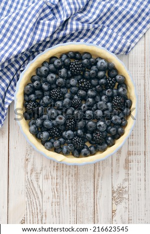Tasty homemade pie with blueberries and blackberries on wooden table. Top view. - stock photo