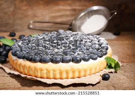Tasty homemade pie with blueberries on wooden table - stock photo