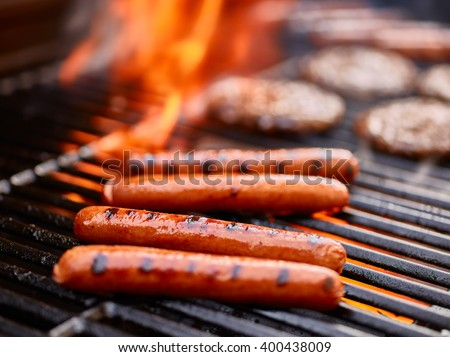 tasty hot dogs cooking on grill with hamburgers - stock photo