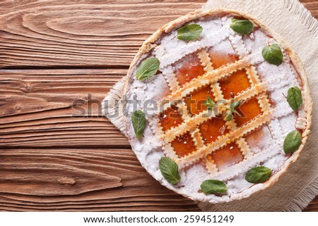Tasty Italian tart with apricot jam and mint on a wooden table. horizontal view from above - stock photo