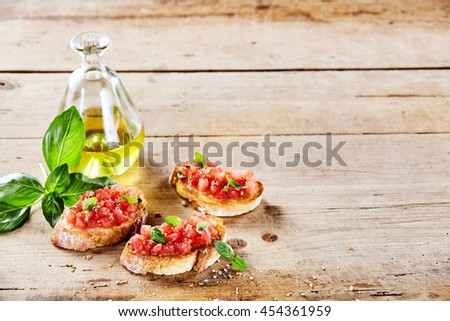 Tasty Italian tomato bruschetta with olive oil on toasted slices of baguette served with fresh basil on a rustic wooden table with copy space - stock photo