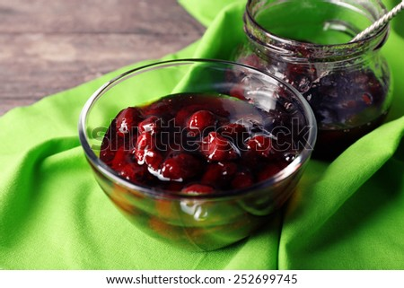 Tasty jam in jar and bowl with napkin on table close up - stock photo
