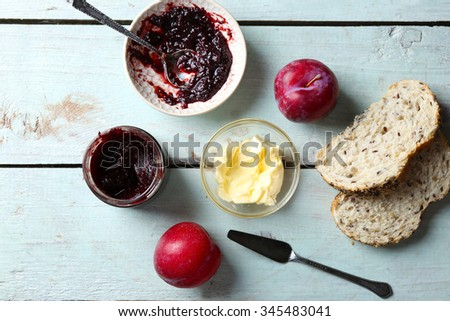 Tasty jam in the jar and bowl, butter, fresh bread, plums and tablet on blue wooden background - stock photo
