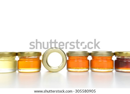 Tasty jars of jam and honey in a row with blank text space isolated on white background - stock photo