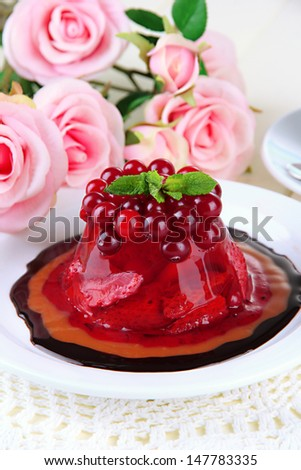 Tasty jelly dessert with fresh berries, on pink roses background