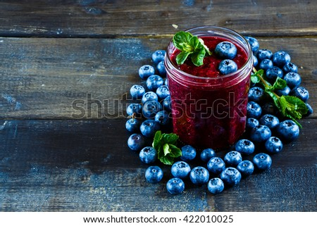 Tasty juicy blueberry smoothie with fresh berry in the glass jar on dark wooden background with space for text, selective focus. - stock photo