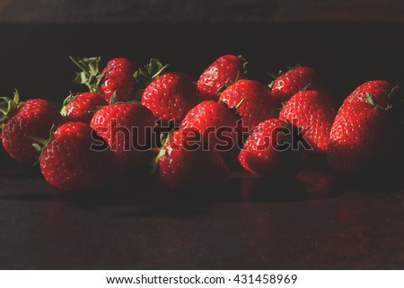 Tasty juicy strawberries on the black table. Red fresh strawberries background. Rich summer strawberry crops, organic farming - stock photo