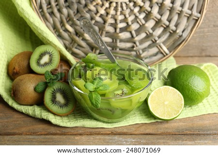 Tasty kiwi jam in glass bowl on wooden table, on wicker mat background - stock photo