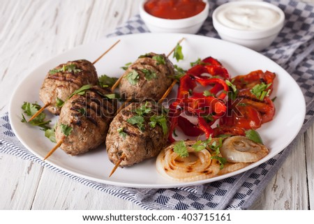 Tasty kofta kebab with grilled vegetables on a plate and sauce close-up on the table. horizontal