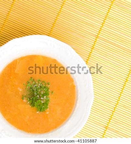 Tasty kohlrabi soup on orange table cover. - stock photo